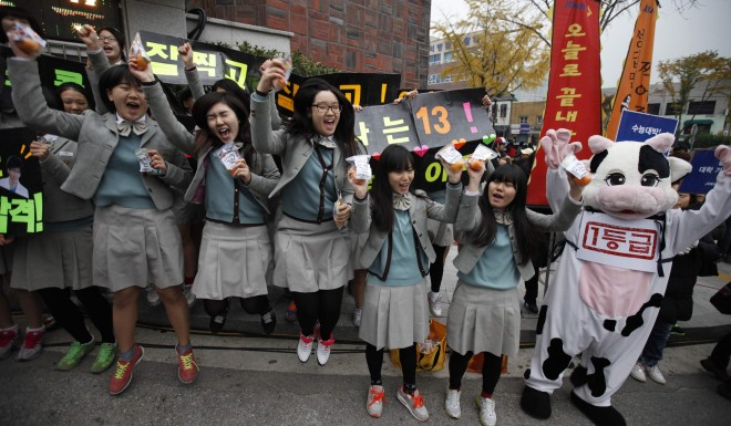 Students from a high school cheer for their seniors in front of a college entrance exam hall in Seoul, South Korea in 2012.