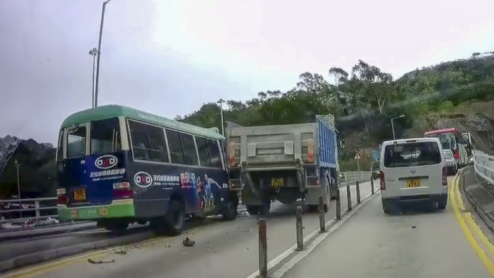 Hong Kong minibus slams into railings, throwing driver from ...