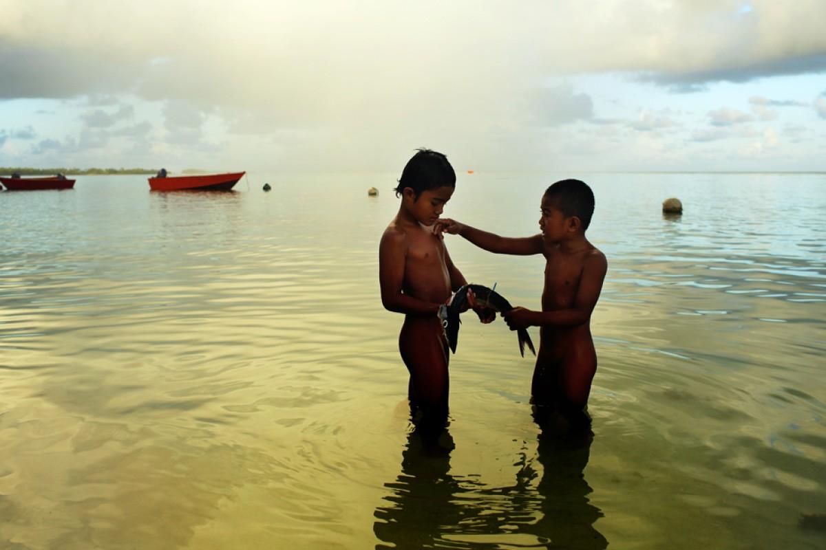 Children dine on raw fish in Funafuti, Tuvalu.