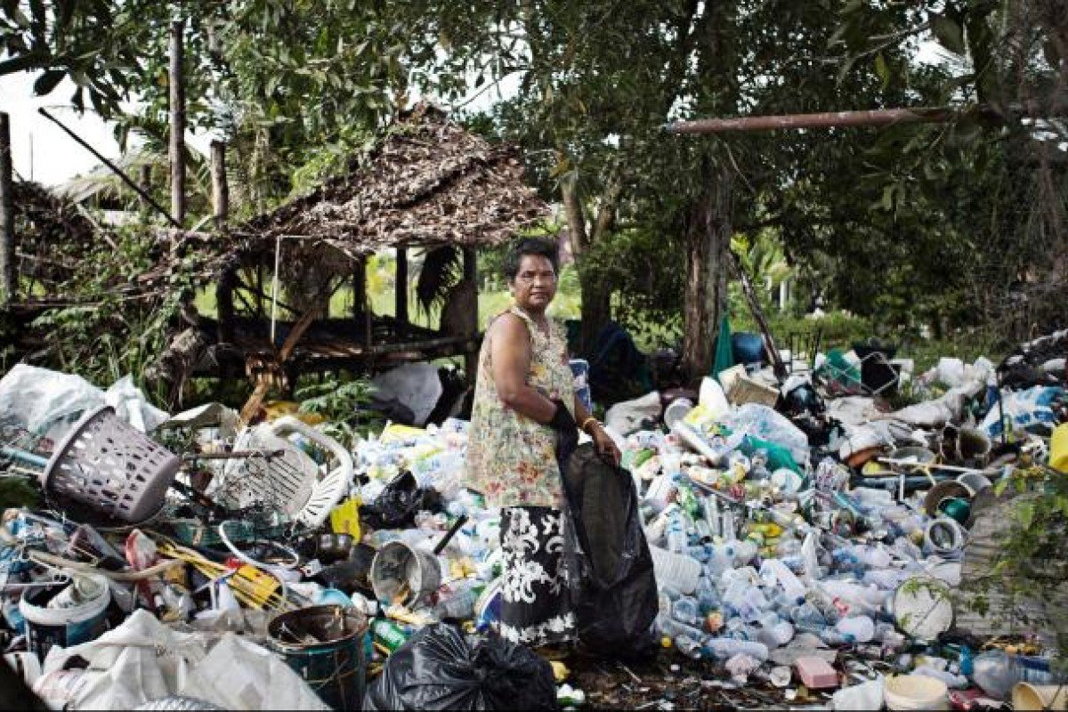A Moken woman scavenges for recyclables on Khao Lak, Thailand.
