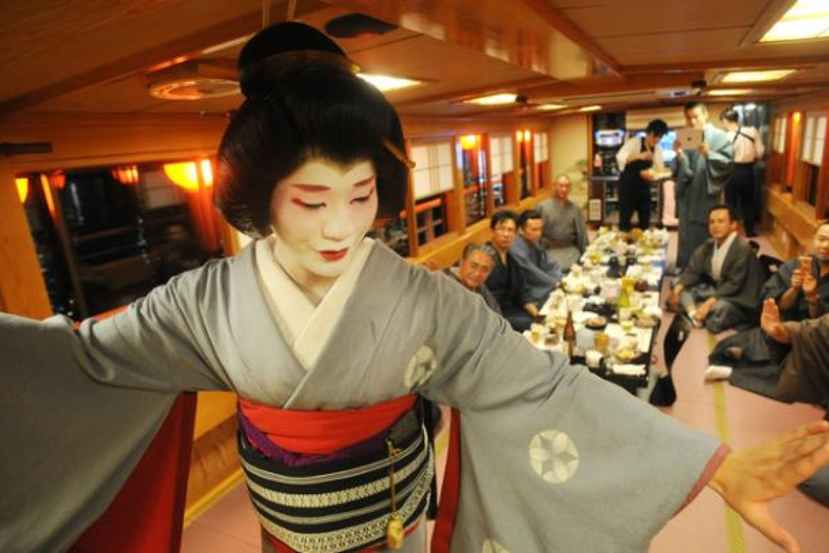 Eitaro performs a dance aboard a boat on the Sumida River in Tokyo.