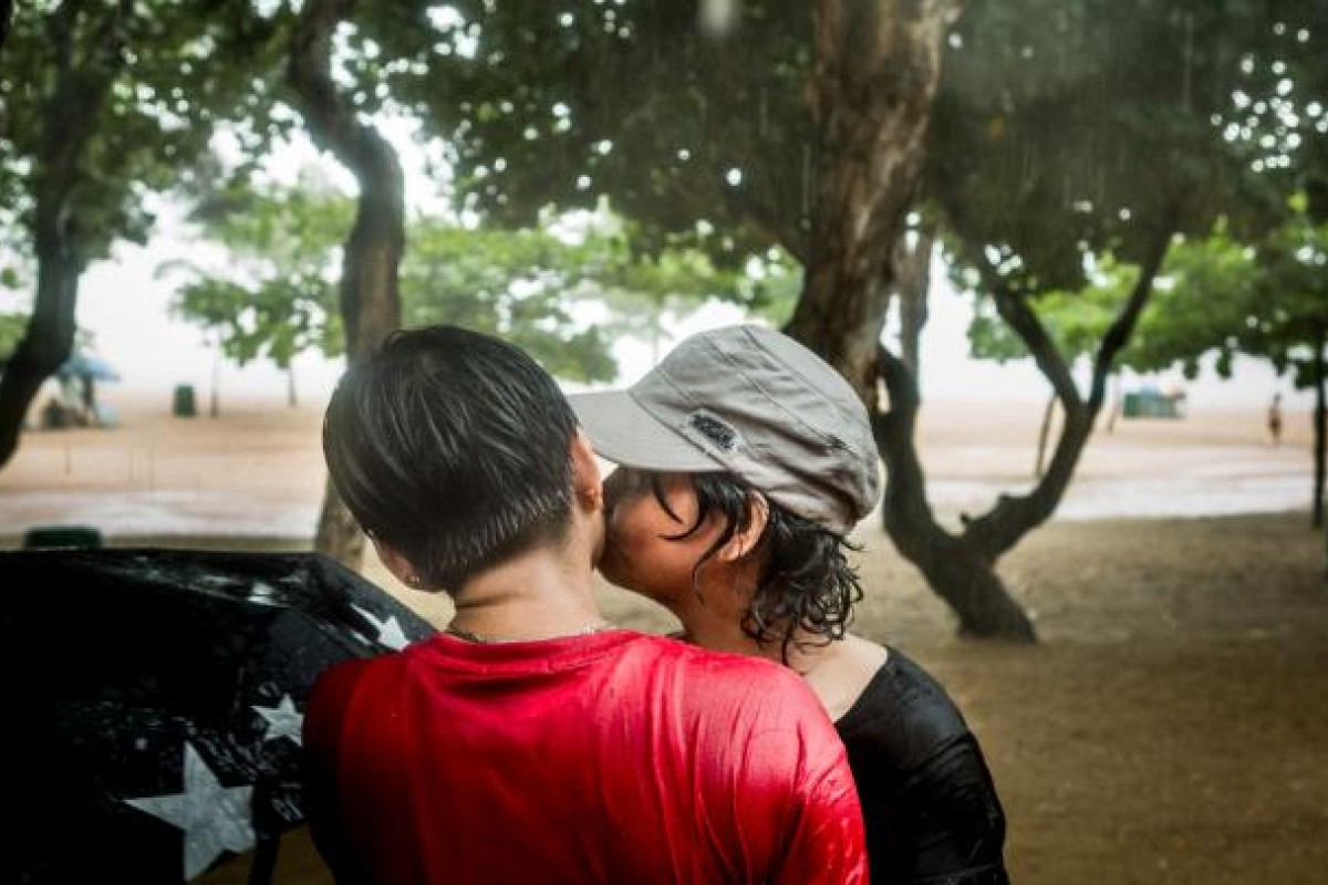 A couple from the Filipino lesbian group Filguys share an intimate moment at a birthday party.
