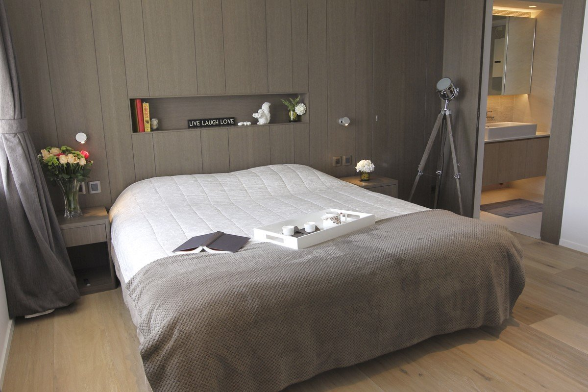 """Master bedroom: The bed (HK$12,000, including side tables) and the wall-panelling units (price on application) were all built by Winfull. The tripod light cost about HK$1,300 from Home Essentials (33 Lyndhurst Terrace, Central, tel: 2870 1400). The """"live laugh love"""" sign was bought in Singapore."""