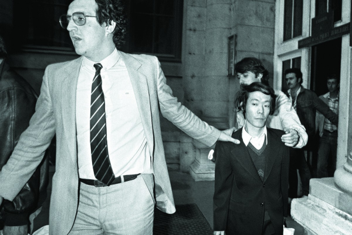 Escorted by plainclothes policemen, Sagawa leaves the Paris Prefecture of Police Headquarters after questioning, on June 17, 1981.