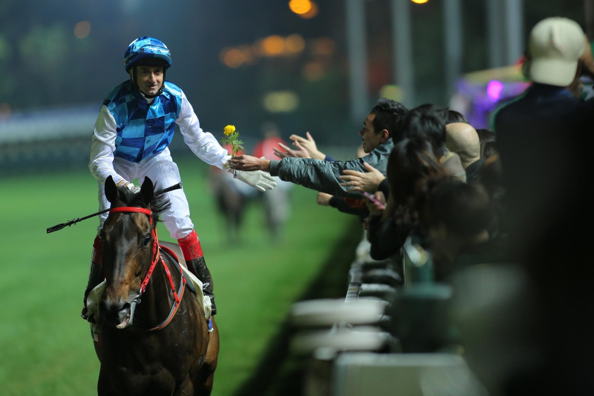 Douglas Whyte receives a flower from a fan after winning the January Cup aboard Pleasure Gains at Happy Valley. Photos: Kenneth Chan
