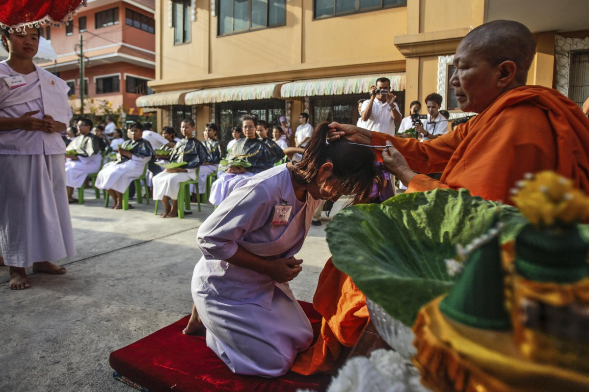 Venerable Dhammananda cuts the hair of a samaneri, or novice in the clergy, at the Songdhammakalyani temple, outside Bangkok.