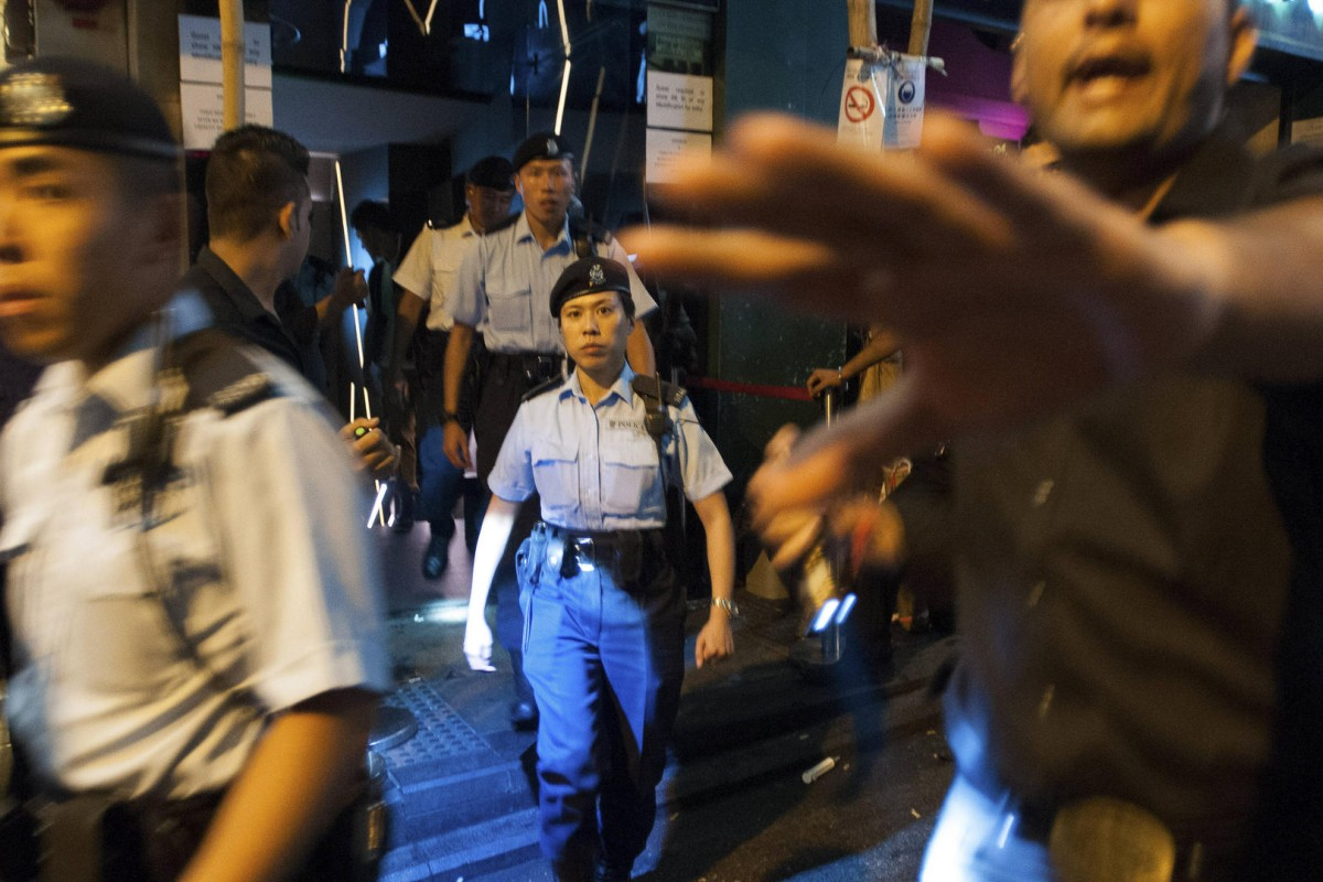 A bouncer at Lan Kwai Fong club Volar tries to hold people back as undercover and uniformed police officers exit the premises after searching customers for drugs in the early hours of September 19.