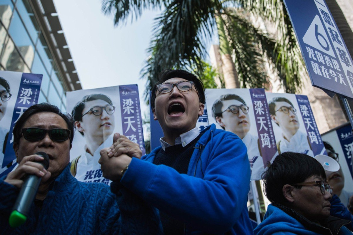 """Hong Kong activist Edward Leung (centre), one of the leaders of """"localist"""" group Hong Kong Indigenous, shouts slogans as he campaigns next to his endorser, local lawmaker Raymond Wong (left), during the New Territories East by-election in February. Photo: AFP"""