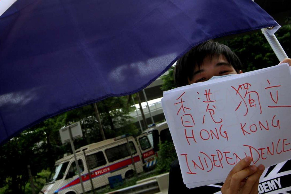 """A member of """"We are Hongkongers, Not Chinese"""" waves the colonial Hong Kong flag outside the central government's liason office in Western district on October 1, 2012. Picture: Dickson Lee"""