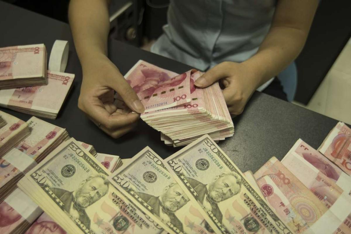 A Chinese clerk counts US dollar and yuan banknotes at a bank in Nantong city, Jiangsu province, China. Photo: AFP