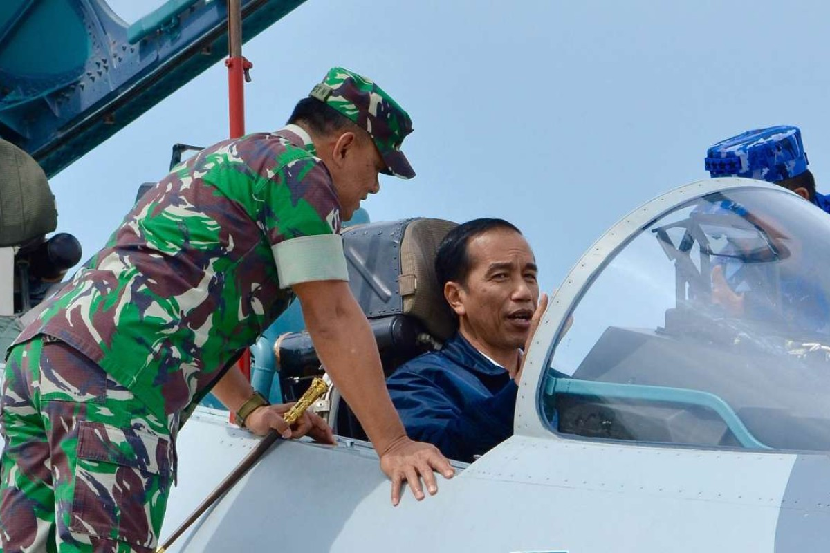 Indonesian President Joko Widodo sits in the cockpit of a Sukhoi Su-30 aircraft next to his military chief Gatot Nurmantyo. Photo: AFP