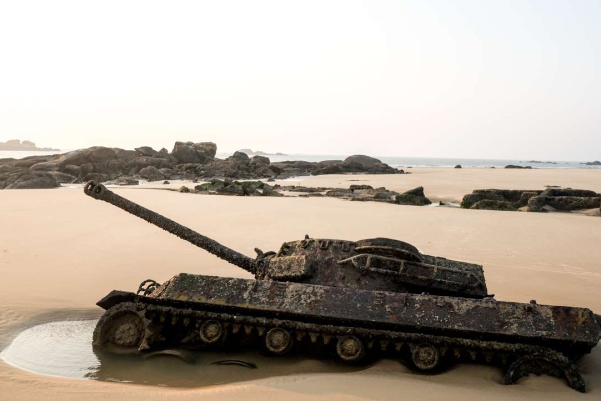 A tank half buried in the sand on a beach in Kinmen emerges from the ground at low tide. Photo: Sim Chi Yin / VII