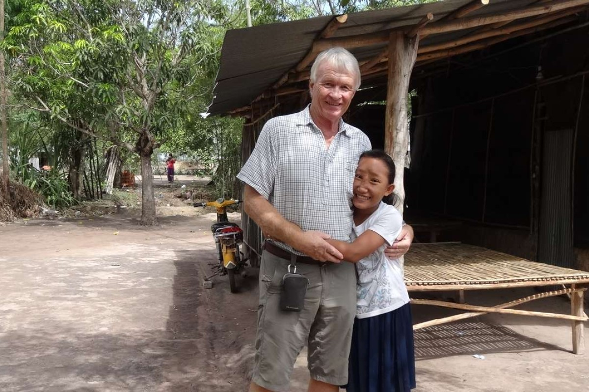Chantrea, who had a meningoencephalocele (MEC), was trafficked as a beggar before being spotted by Jock Struthers at Cambodia's border with Vietnam, in 2012. She is seen here with Struthers, in June 2016, at her family's home. Pictures: courtesy of Jock Struthers and the Children's Surgical Centre