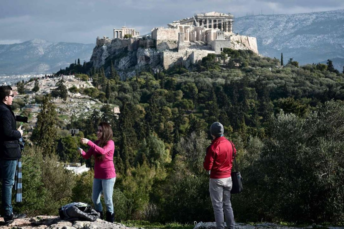 Tourists watch the Acropolis from the Pnyx hill in Athens, Greece. Photo: AFP