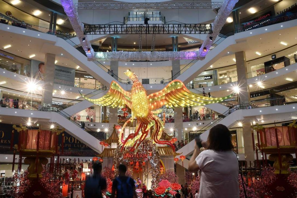 Visitors walk past a giant rooster installation as part of upcoming Lunar New Year celebrations at a shopping mall in Kuala Lumpur. Photo: AFP