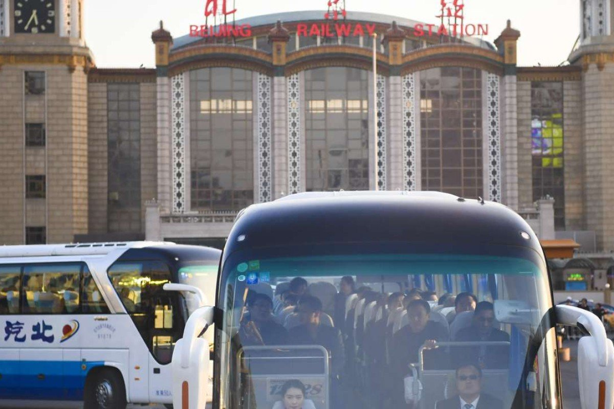 Deputies to the 12th National People's Congress from northeast China's Liaoning Province head for their accommodation by bus after arriving at Beijing Railway Station in Beijing. Photo: Xinhua