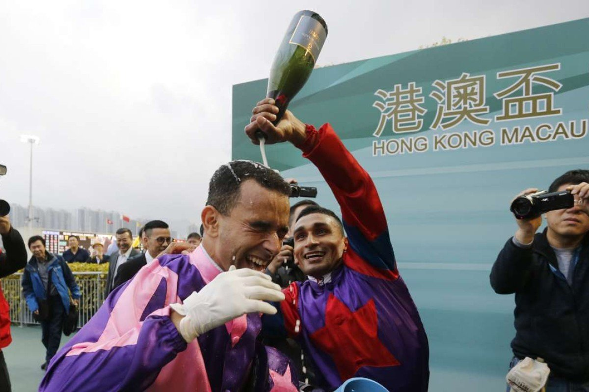 Joao Moreia is doused by champagne by fellow jockey Karis Teetan after notching his eighth win of the day aboard Prawn Baba. Photos: Kenneth Chan