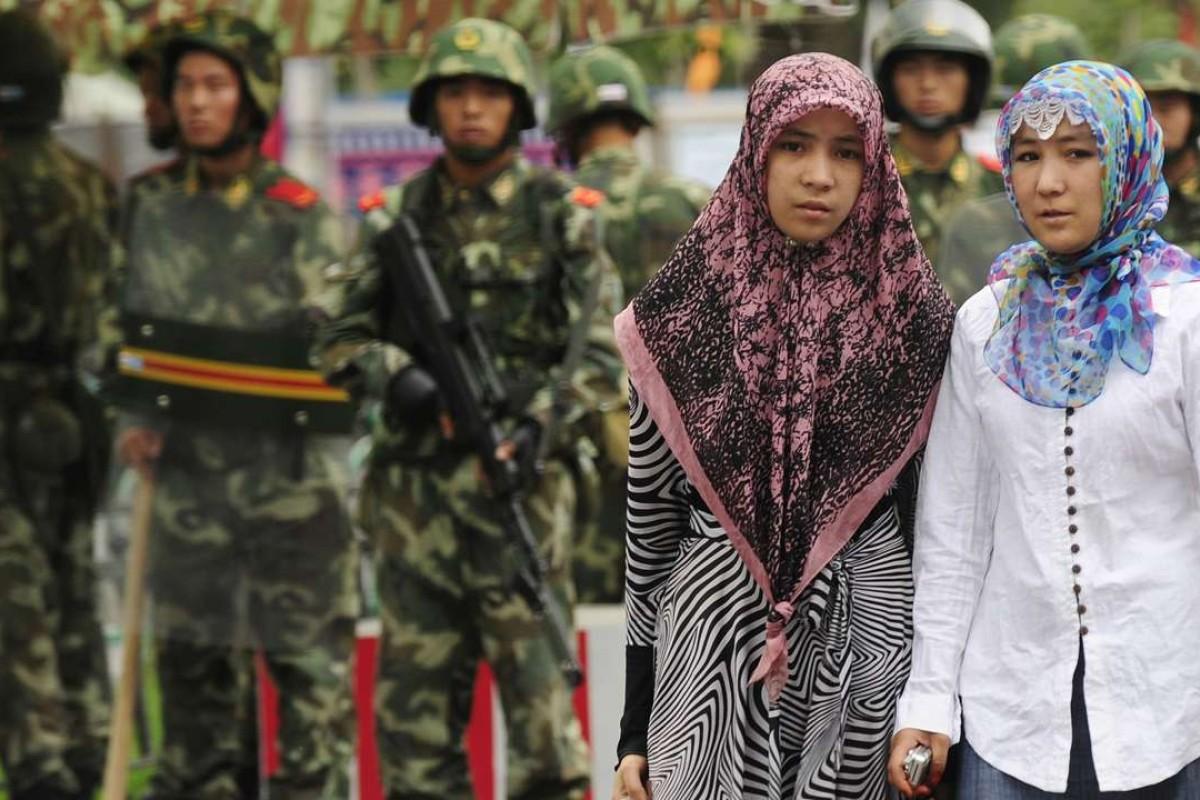Two Uygur women walk past paramilitary policemen standing guard outside the Grand Bazaar in Urumqi, Xinjiang. Photo: AFP