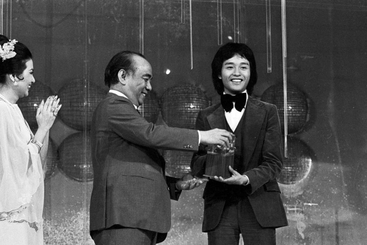 Leslie Cheung Kwok-wing (right), the first-runner up of the Asian Amateur Singing Contest, received his trophy gleefully, May 1977.