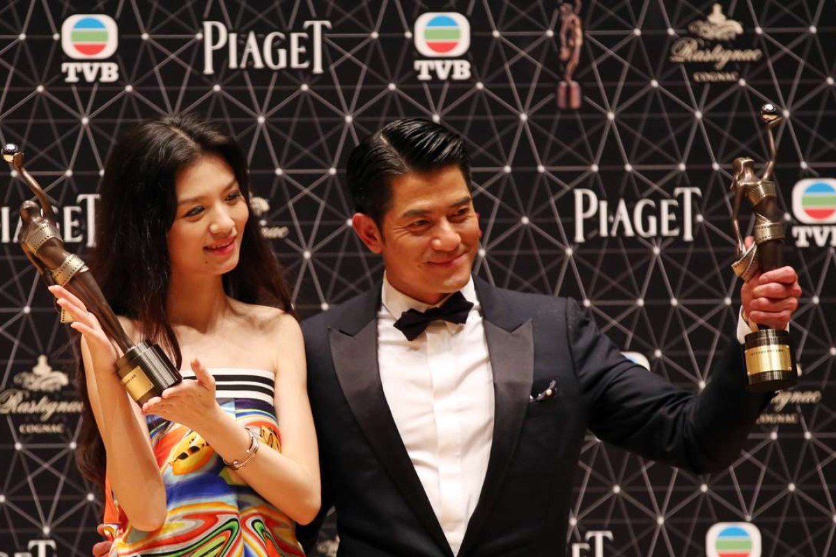 """(L to R) Jessie Li and Aaron Kwok Fu-shing celebrate after winning the best actress and the best actor award for their roles in movie """"Port of Call"""" at the 35th Hong Kong Film Awards."""