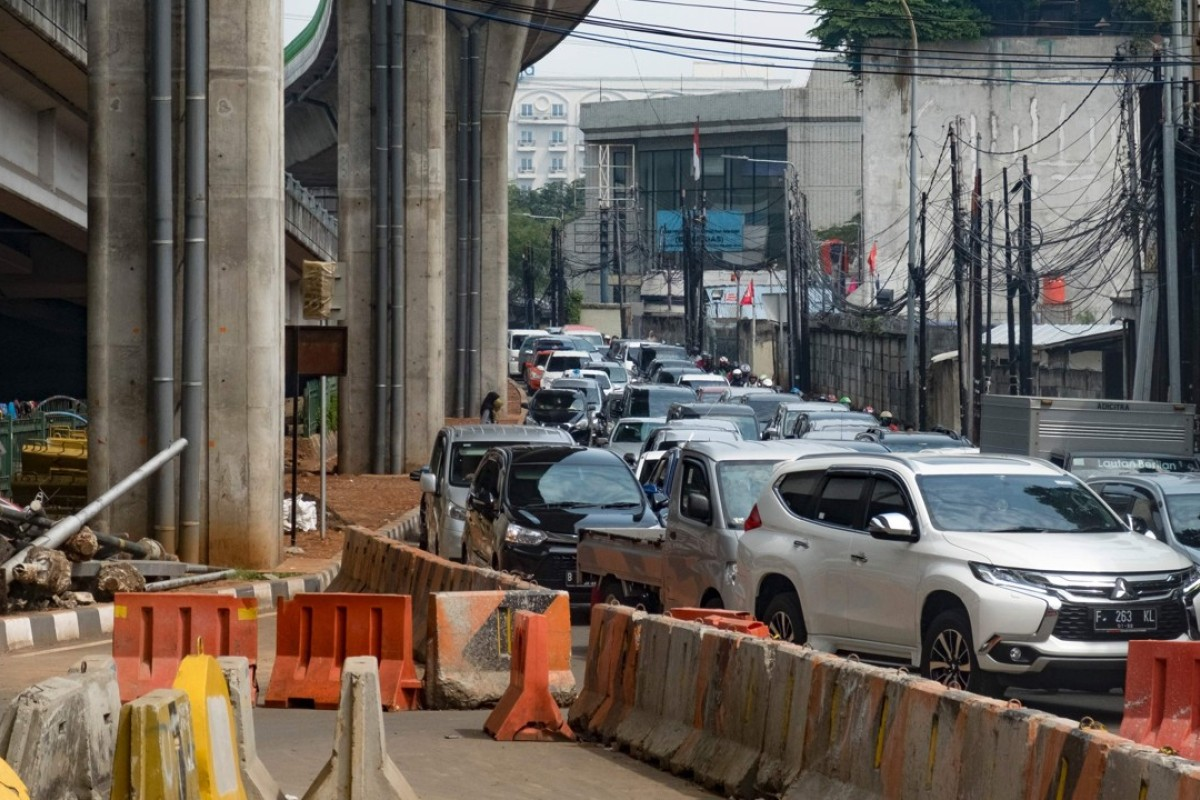 Vehicles pack a narrow road next to an under-construction flyover in Jakarta. Photo: AFP
