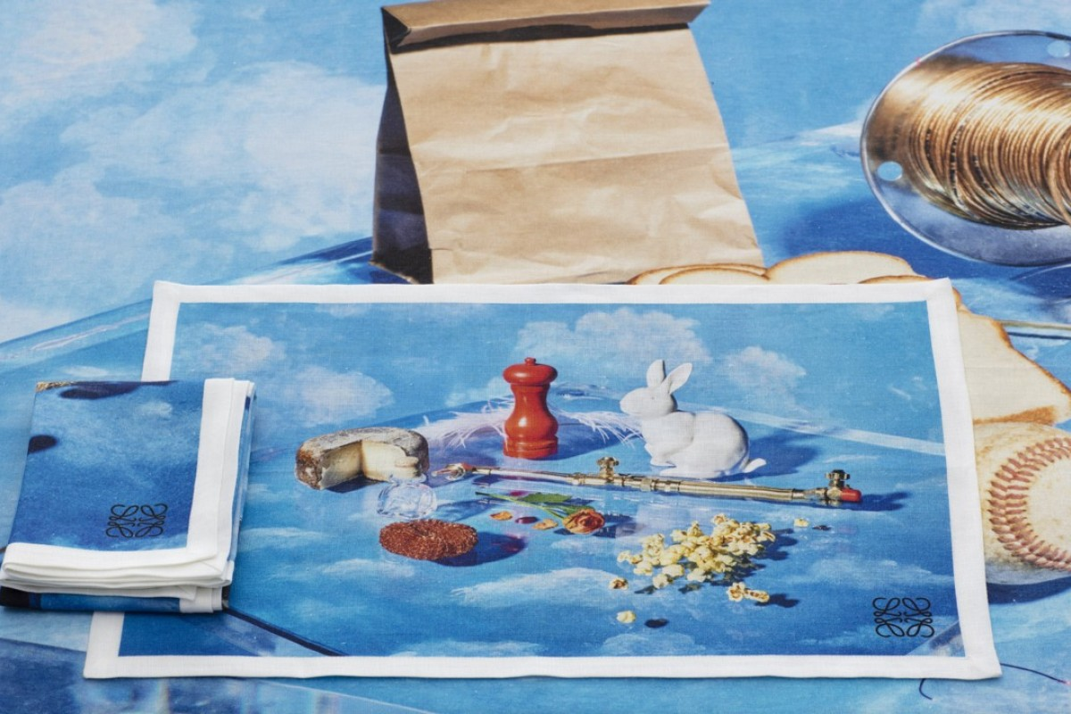 The table linen features photographed objects against a painted cloudscape backdrop