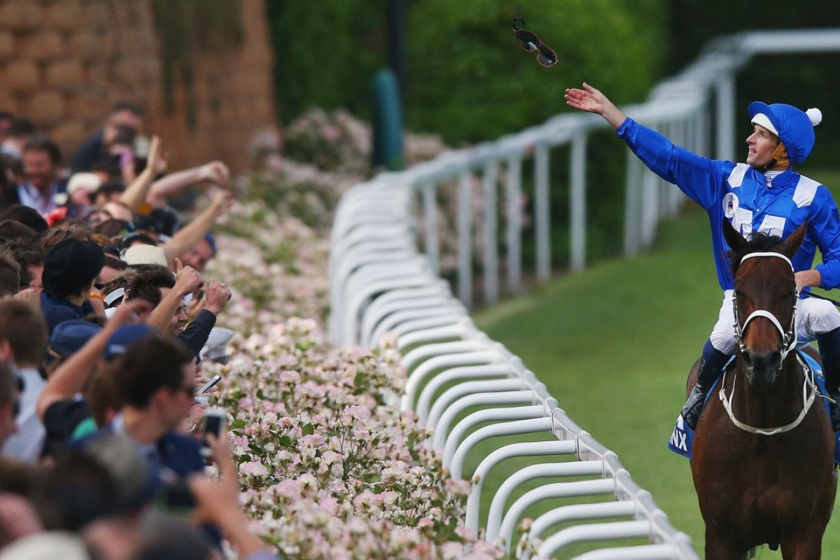 Hugh Bowman throws his googles into the crowd after Winx wins the 2015 Cox Plate. Photo: Michael Dodge/Getty Images