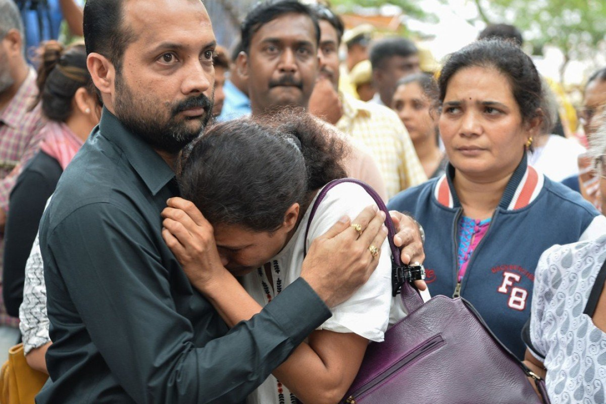 Indian journalist Gauri Lankesh's sister Kavitha Lankesh is consoled by a relative as her body is brought to the Ravindra Kalakshetra cultural centre in Bangalore. Photo: AFP