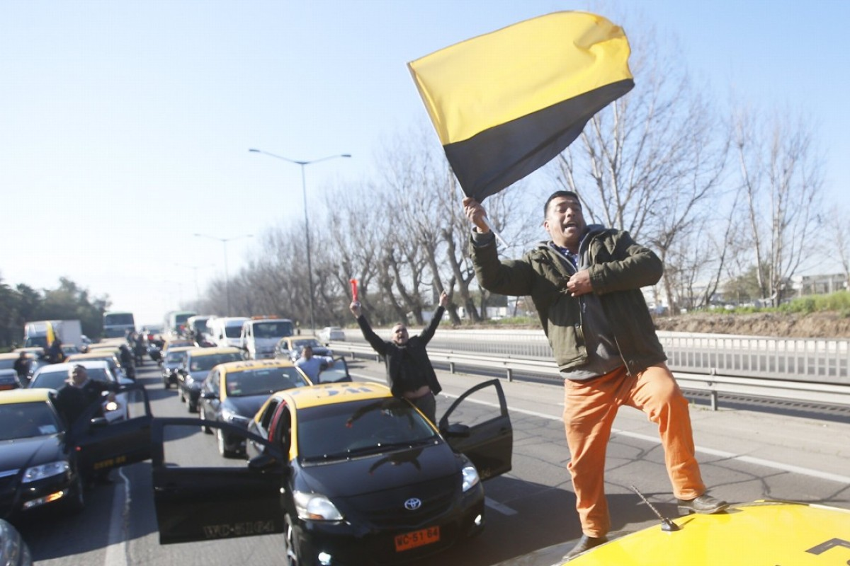 Taxi drivers block the access to the airport, during a protest in Santiago, Chile against the operation of the companies Uber and Cabify in the country. Ride-sharing companies are facing huge growth potential, and significant backlash, worldwide. Photo: EPA