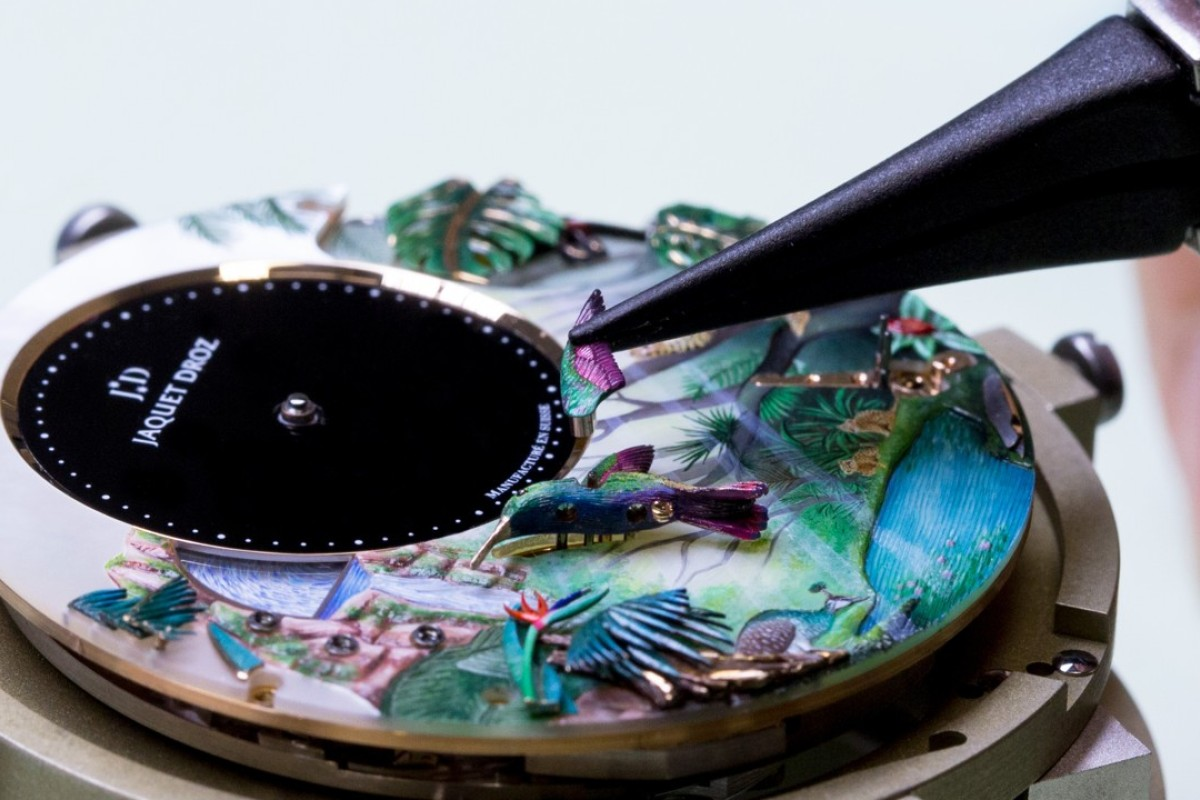 The dial of the Tropical Bird Repeater watch by Jaquet Droz. An artisan delicately attaches a fluttering wing to the hummingbird.