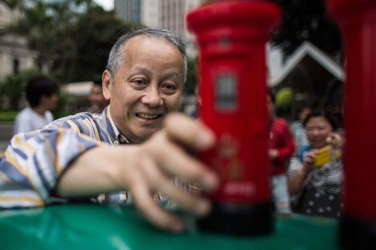 A Hongkonger with a toy colonial-era British mail box souvenir. Photo: AFP