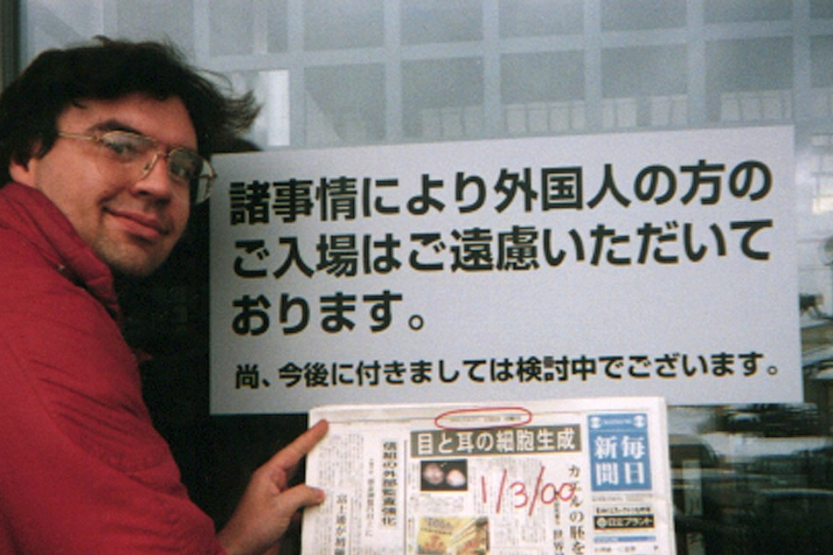 Debito Arudo in front of a Japanese bathhouse with a sign saying 'Japanese Only'. Photo: Julian Ryall