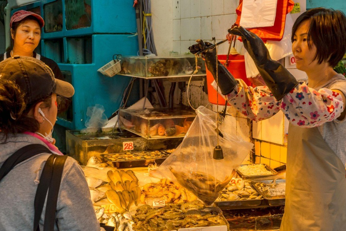 A seafood vendor weighs shrimp at a market in Hong Kong.