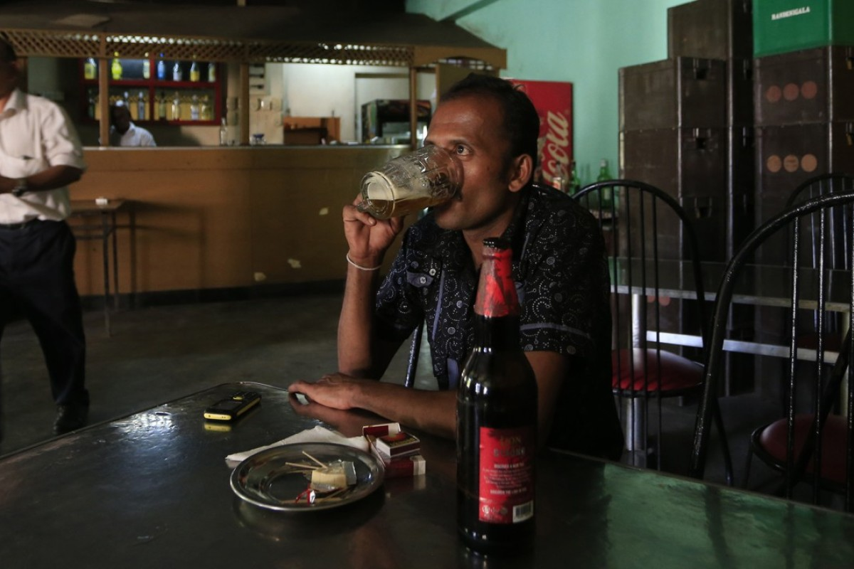 A Sri Lankan man drinks beer at a bar in Colombo. Sri Lanka revoked a 38-year ban on selling alcohol to women, only to reverse the decision a few days later. Photo: AP