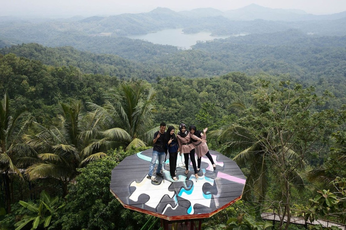 Visitors pose on a platform at the Pulepayung tourist attraction in Kulon Progo regency, special region of Yogyakarta, Indonesia. Photo: Bloomberg