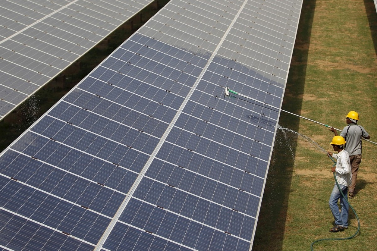 Workers clean a solar power plant in Gujarat, India. Photo: Reuters