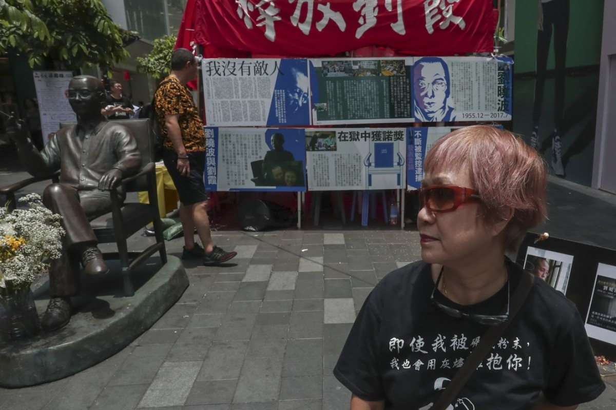 Activist Vivian with the statue of Liu Xiaobo on Paterson Street, in Causeway Bay. Picture: Jonathan Wong