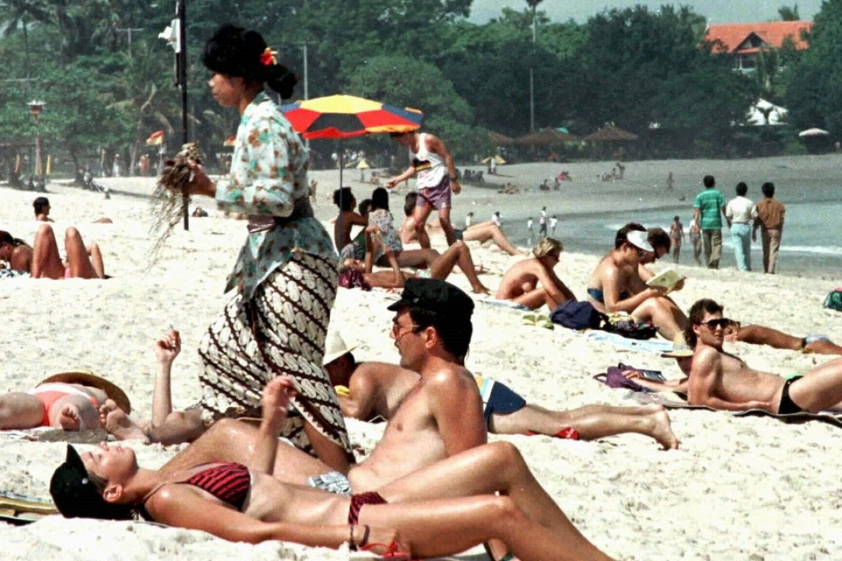 A Balinese woman in traditional dress walks past foreign tourists sunbathing on Kuta Beach on the Indonesian island of Bali in 1996 when mass tourism was in full swing. Picture: Reuters