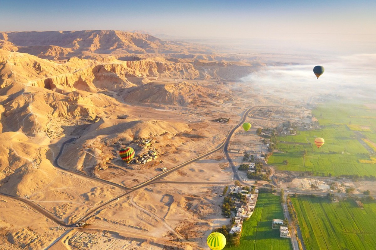 A hot air balloon flights over the west bank of the Nile, landscape of mountains and green valley