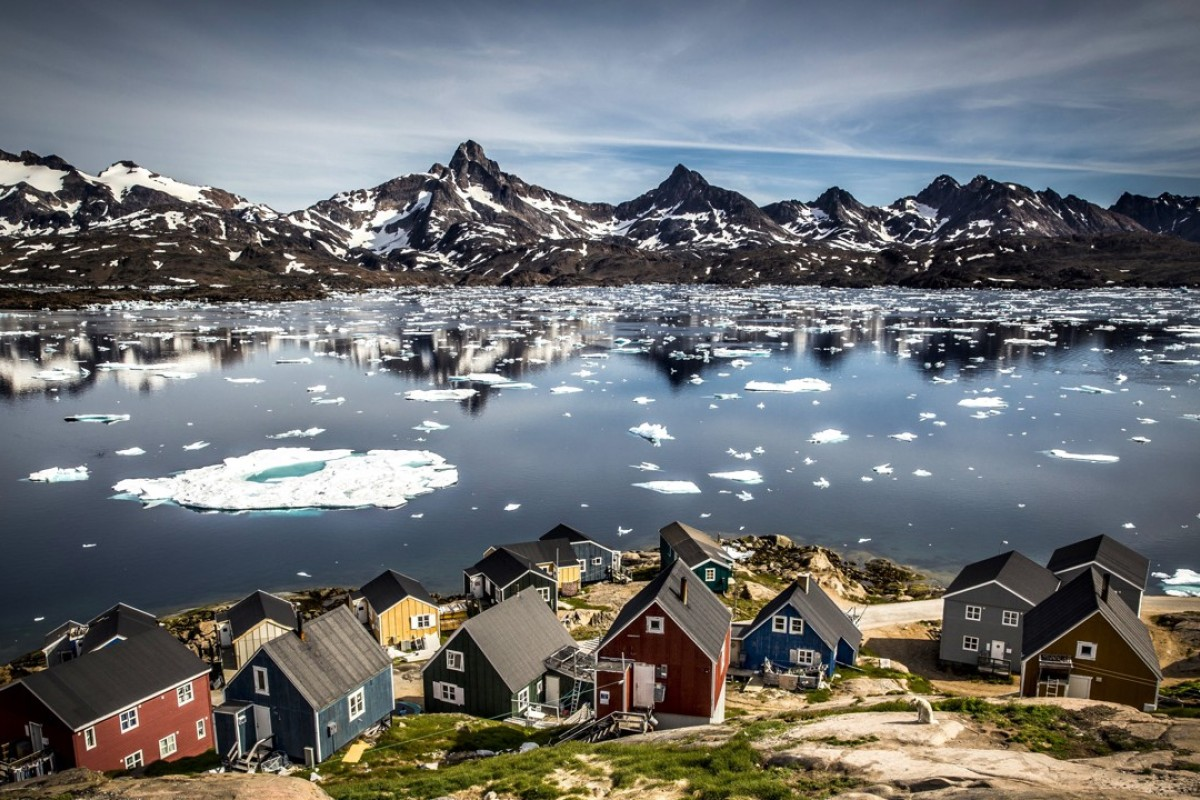 Houses in Tasiilaq at the edge of Kong Oskars Havn with the mountain Polheim in the background.