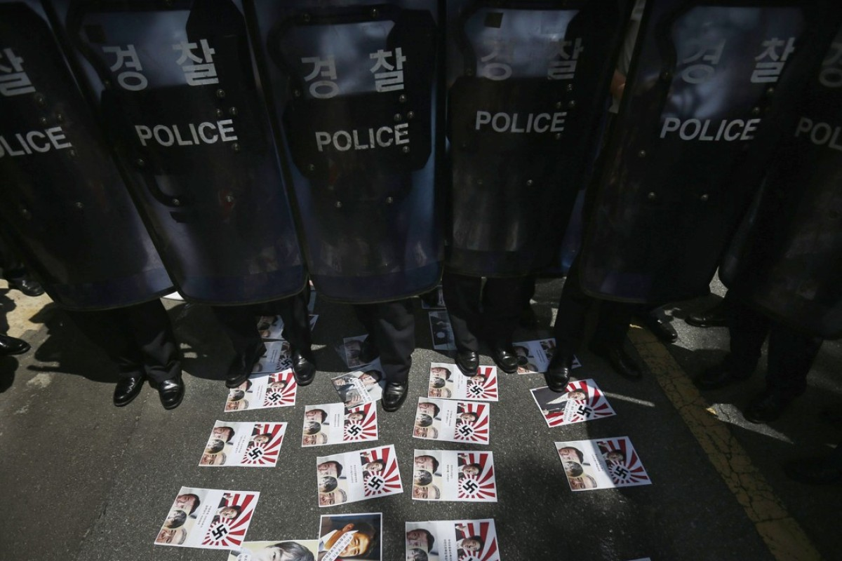 South Korean police at an anti-Japan protest. On the ground are leaflets featuring the Rising Sun flag, which is seen by many in Asia as a symbol of Japan's colonial period. Photo: Reuters