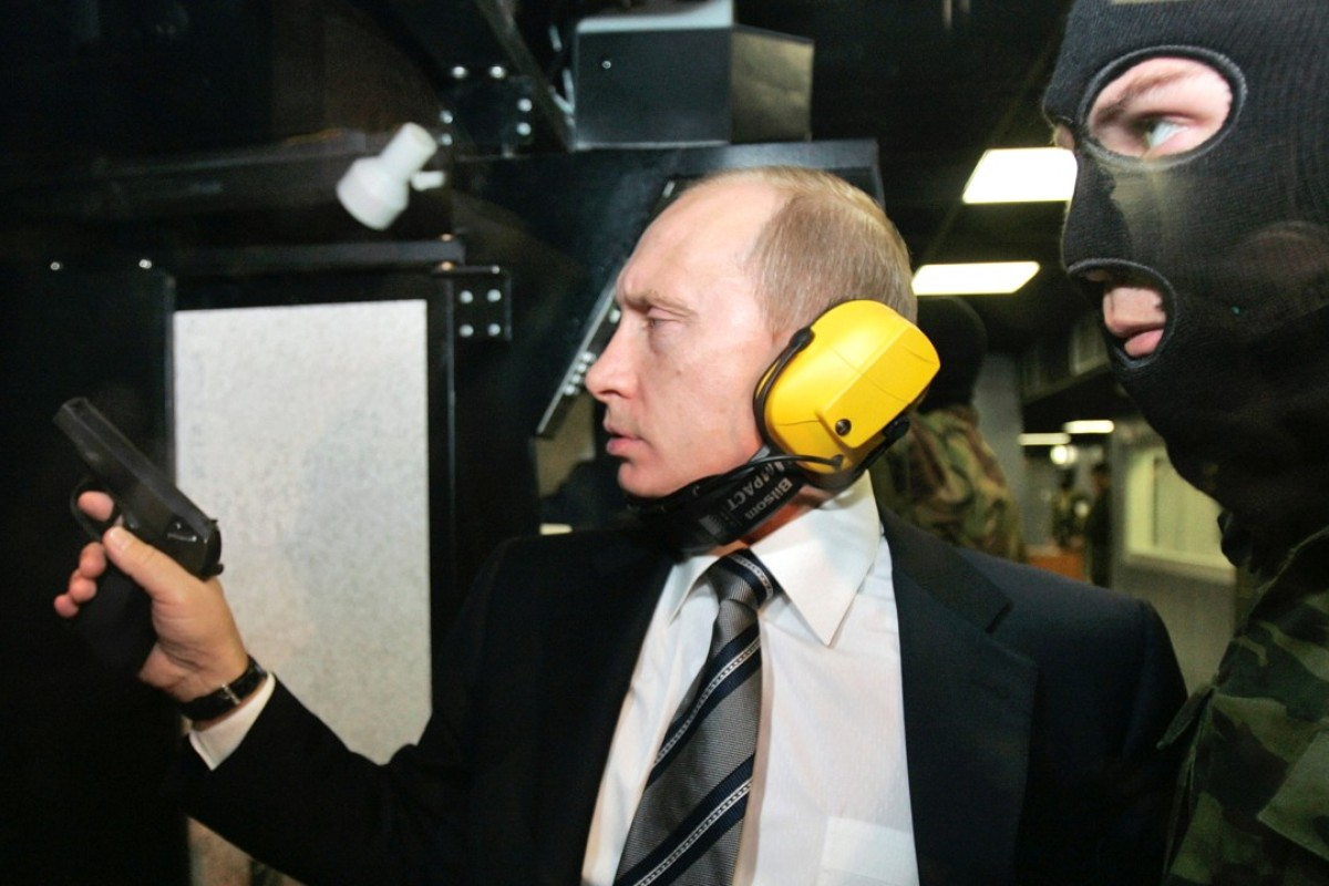 Russian President Vladimir Putin and a masked security officer at a shooting gallery in Moscow. Photo: Reuters
